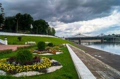Vista da cama de flor do beira-rio no parque da cidade e da ponte velha no fundo, cidade de Volga de Tver, Rússia Foto de Stock