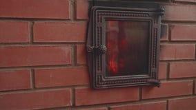 Vista da chama do fogo na chaminé A mão do ` s do homem fecha a porta da chaminé Opinião de movimento lento vídeos de arquivo