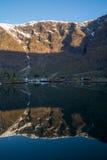 Vista da cidade de Flam, Noruega com o contexto cênico da montanha que reflete na água Fotografia de Stock Royalty Free