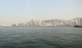A vista da cidade de Hong Kong e o mar com uma flutuação enviam Panorama da cidade na tarde architectural fotografia de stock royalty free