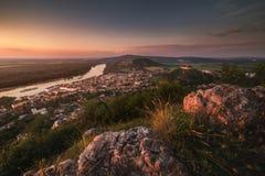 Vista da cidade e do rio pequenos com as rochas no primeiro plano no por do sol imagens de stock