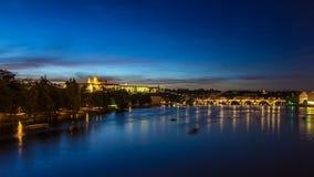 Vista da cidade Praga em República Checa com dia colorido dos barcos de pá ao timelapse da noite no rio de Vltava com filme