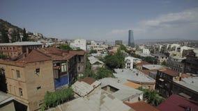 Vista da cidade velha de Tbilisi da parte, Geórgia, com os telhados de construções velhas e modernas, arranha-céus de vidro filme
