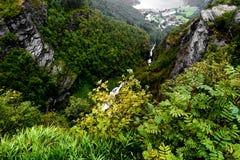 Vista da cimeira das montanhas em torno de Geiranger e do fiorde com um abismo profundo, de penhascos e de um rio na parte inferi Imagens de Stock