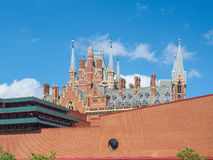 Vista da construção de British Library com as torres góticos da estação de St Pancras atrás da parede Imagem de Stock Royalty Free