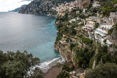 A vista da costa de mar com formação de espuma acena em uma praia e em uma cidade pequena fotos de stock royalty free