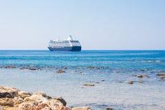 Vista da costa de mar com pedras e do barco em Chania, ilha da Creta, Grécia Foto de Stock