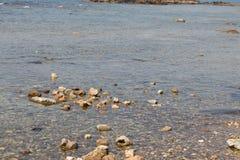 Vista da costa de mar com pedras e do barco em Chania, ilha da Creta, Grécia Imagens de Stock