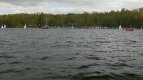 Vista da curva do barco quando mover-se rápido sobre a água com regata no fundo vídeos de arquivo