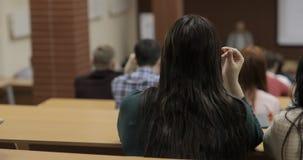 Vista da dietro di grande gruppo misto di etnia di studenti in un'aula, studenti interessati a conferenza l'ascolto stock footage