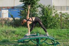 vista da dietro di una giovane donna che fa posa di yoga del triangolo fotografia stock