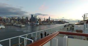 Vista da doca às construções em New York, turistas no navio de cruzeiros que tem uma boa estadia e que olha New York filme