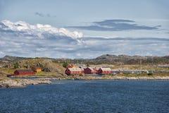Vista da estrada atlântica às casas vermelhas pequenas no oceano, Noruega Foto de Stock