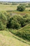 Vista da inclinação do penhasco através do vale à vila Fotografia de Stock Royalty Free