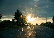 Vista da janela de carro na estrada adiante durante o por do sol bonito fotografia de stock royalty free