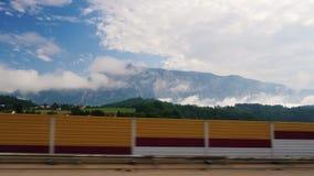 A vista da janela de carro nos cumes bonitos ajardina em Áustria O carro monta rapidamente após uma barragem ou uma cerca vídeos de arquivo