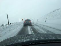 Vista da janela de carro que conduz na queda das nevadas fortes durante o curso do inverno do trabalho para dirigir foto de stock