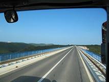 Vista da janela do ônibus em uma estrada vazia e nas montanhas cobertas com as florestas fotos de stock royalty free