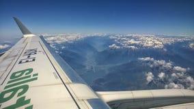 Vista da janela do avião das montanhas com neve na parte superior, nas nuvens, na asa e no céu azul Fotos de Stock Royalty Free