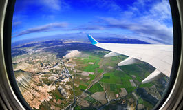 Vista da janela do avião em campos e em montanhas imagens de stock