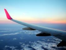 Vista da janela dos aviões, da asa do avião com céu azul e da nuvem no tempo do por do sol Fotos de Stock