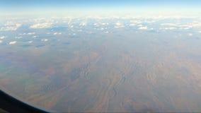 Vista da janela dos aviões que mostra cordilheiras vermelhas da terra vídeos de arquivo