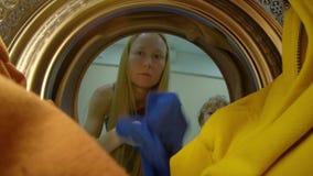 Vista da m?quina de lavar como uma jovem mulher p?e a roupa suja nela filme