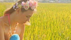 Vista da menina em Garland Smelling Rose à grama verde filme