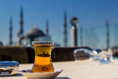 Vista da mesquita azul (Sultanahmet Camii) através de um vidro turco tradicional do chá, Istambul, Turquia Imagens de Stock Royalty Free