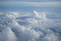 Vista da nuvem branca densa de forma livre bonita com máscaras do fundo do céu azul da janela do plano do voo Foto de Stock