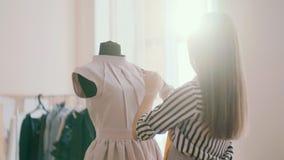 Vista da parte de trás de um desenhador de moda que endireite a camisa de uma mulher em um manequim video estoque
