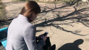 A vista da parte de trás de uma menina em um revestimento cinzento que se sente em um banco e se use o telefone video estoque