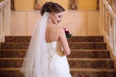 A vista da parte de trás de uma noiva bonita em um vestido de casamento com laço aumenta as escadas, girando ao redor e sorrindo imagens de stock royalty free