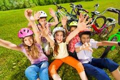 Vista da parte superior das crianças nos capacetes com mãos acima Fotos de Stock