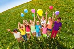 Vista da parte superior de crianças eretas com balões fotografia de stock