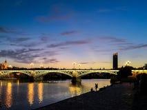 A vista da ponte da ponte de Triana de Isabel II que medem o rio de Guadalquivir em Sevilha iluminou no crepúsculo imagem de stock royalty free