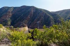 A vista da represa com arbustos e montanhas fotos de stock royalty free