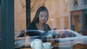 Vista da rua de um chá ou de um café bebendo da jovem mulher do copo branco no café que senta-se na cafetaria perto filme