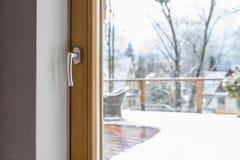 Vista da sala através de uma janela fechado do balcão com um punho em um terraço nevado com uma cadeira de vime e uma balaustrada foto de stock royalty free