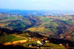 Vista da sopra alle colline della Marche coperte dai campi e dalle foreste fotografia stock