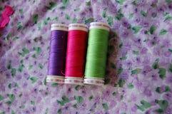 Vista da sopra delle bobine variopinte del filo in porpora, nel rosa ed in verde fotografia stock