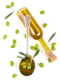 Vista da sopra di un olio d'oliva in bottiglia, in un cucchiaio e in un oli crudo Fotografie Stock Libere da Diritti