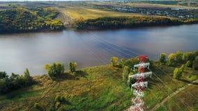 Vista da sopra la linea elettrica sopraelevata di sostegni della struttura sulla banca del lago archivi video