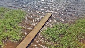 Vista da sopra sopra un pilastro di legno, sulla riva del lago Fotografia Stock