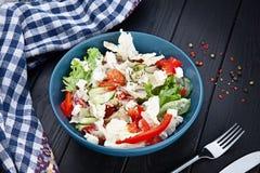 Vista da sopra sulla ciotola fresca e casalinga del vegano insalata vegetariana della lattuga del pomodoro in ciotola blu su fond immagine stock