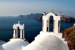 Vista da superfície do mar através do arco branco grego tradicional da igreja com cruz e dos sinos na vila de Oia da ilha de Cycl Imagem de Stock Royalty Free