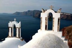 Vista da superfície do mar através do arco branco grego tradicional da igreja com cruz e dos sinos na vila de Oia da ilha de Cycl Foto de Stock Royalty Free