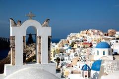 Vista da superfície do mar através do arco branco grego tradicional da igreja com cruz e dos sinos na vila de Oia da ilha de Cycl Fotografia de Stock Royalty Free