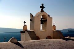 Vista da superfície do mar através do arco branco grego tradicional da igreja com cruz e dos sinos na vila de Oia da ilha de Cycl Imagens de Stock Royalty Free