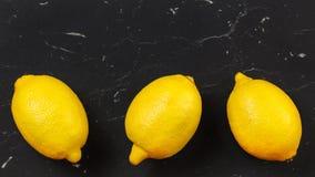 Vista da tavolo, tre interi limoni maturi sul bordo di pietra nero Spazio per testo qui sopra immagine stock libera da diritti